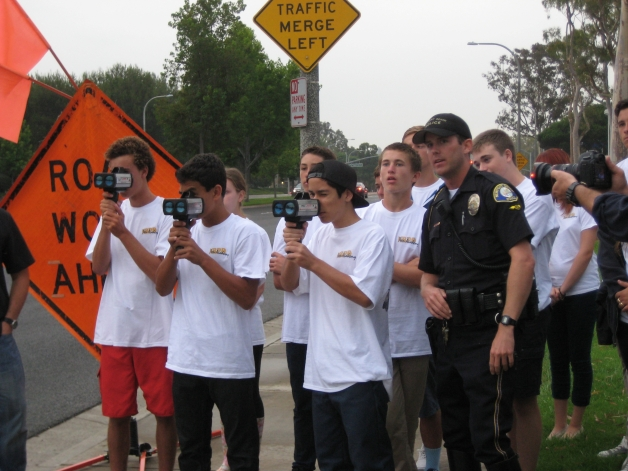Teen Academy students using Lidar (light detection and ranging) guns to gauge motorist speed. Front row, (holding lidar) l to r: Evan Schwartz, Giorgio Weismann, Cesar Guzman with Motor Officer Sean Dugan. Back row: Strom Ossenmacher, Chad Redfearn and Kevin Conde. 2012. Courtesy NBPD.